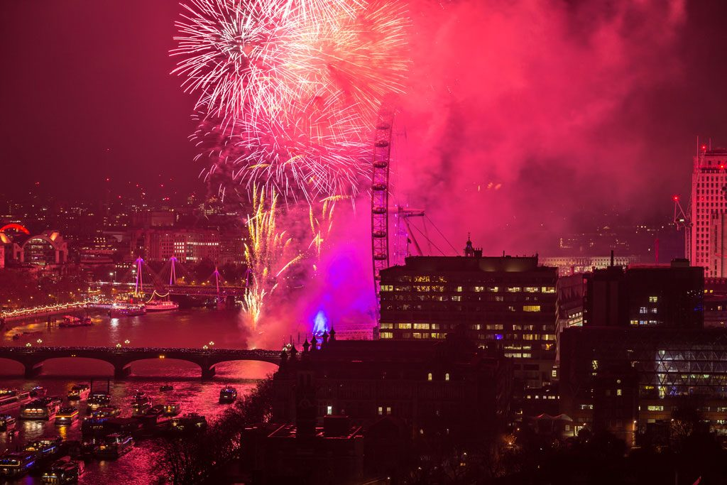 The sky turns purple with smoke as fireworks explode out of the London Eye on New Years Eve