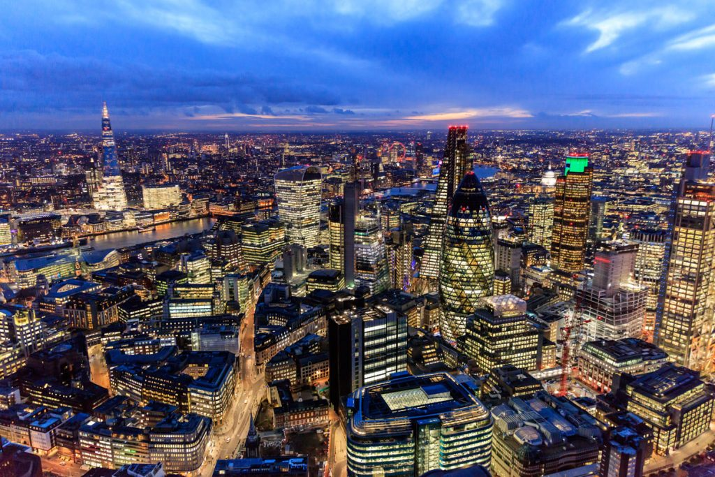 An evening photograph of London City with bright lights