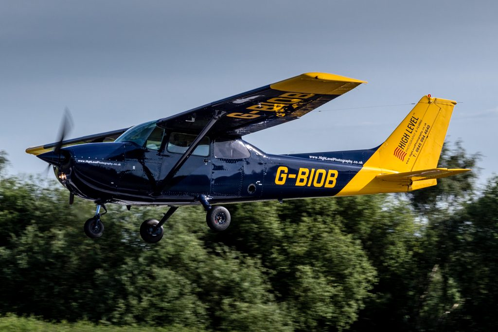 Blue and yellow Cessna 172 with the registration G-BIOB