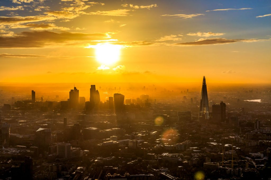 An evening photograph of a silhouetted London skyline with the sun setting behind it