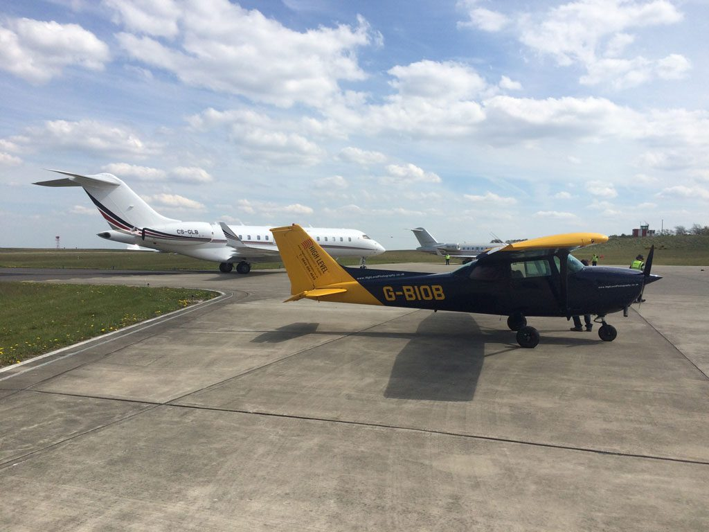 A small light aircraft parked next to the large planes at Leeds Airport